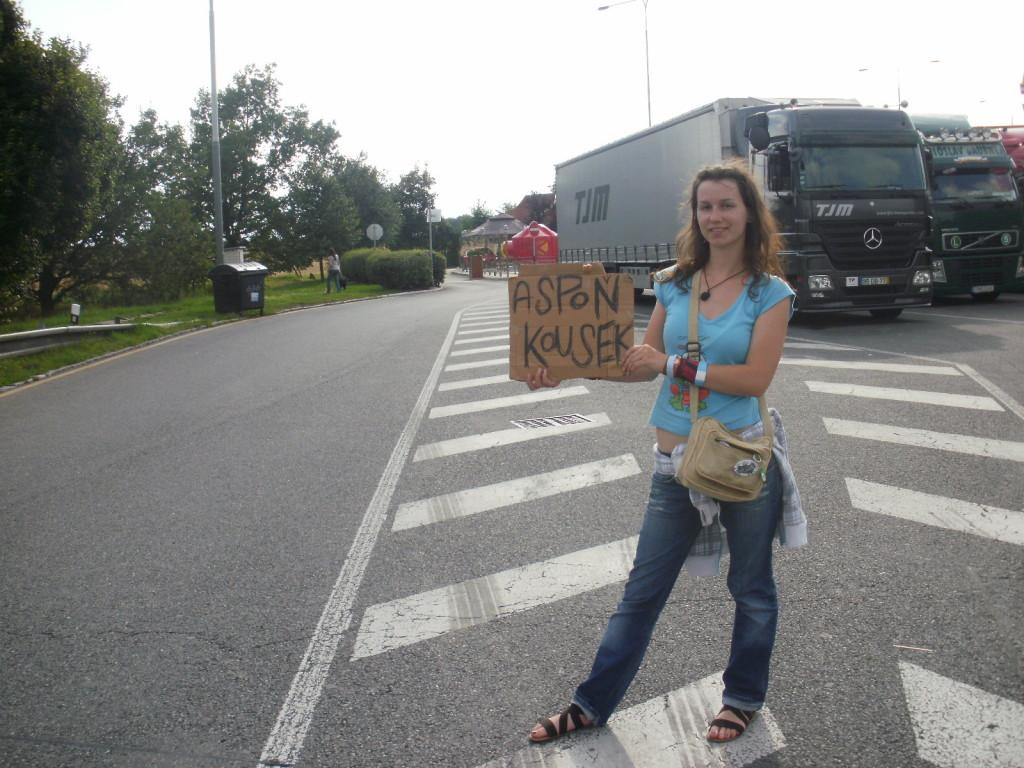 Dívka stopuje u silnice a drží ceduli.