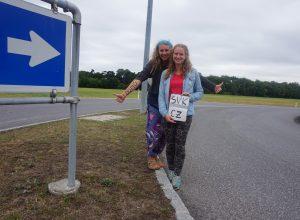Dvě dívky cestují stopem a stojí u silnice se zdviženým palcem.