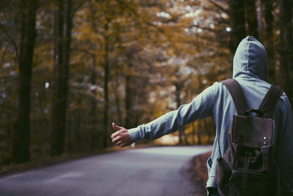 Muž s kapucí stopuje u silnice
